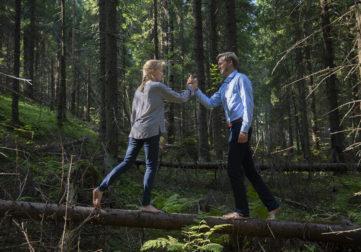 Nainen ja mies tasapainoilevat puunrungolla