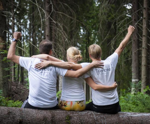 kolme henkeä tuulettaa puunrungolla istuen