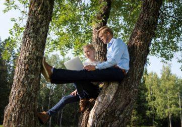 Nainen, mies ja tietokone puussa töissä.