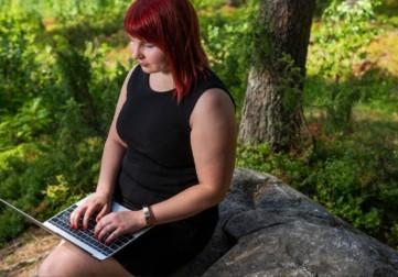 Nainen istuu kivellä ja kirjoittaa tietokoneella.