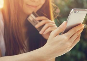 nainen selaa puhelinta hymyillen luottokortti kädessä