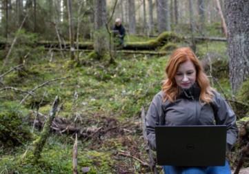 Nainen työskentelee läppärillä metsässä