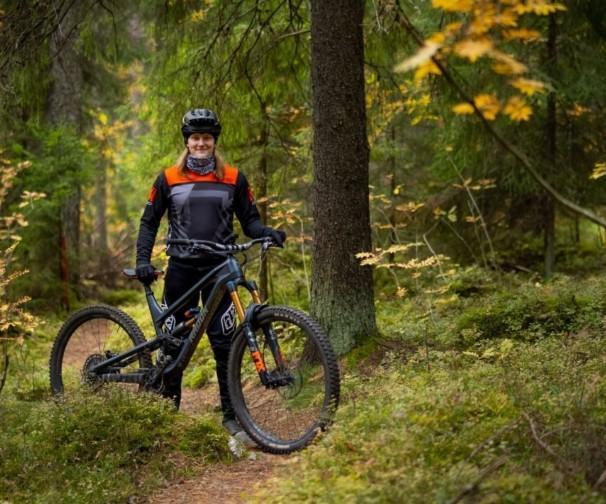 Eero Joensuu seisoo maastopyörän kanssa metsässä
