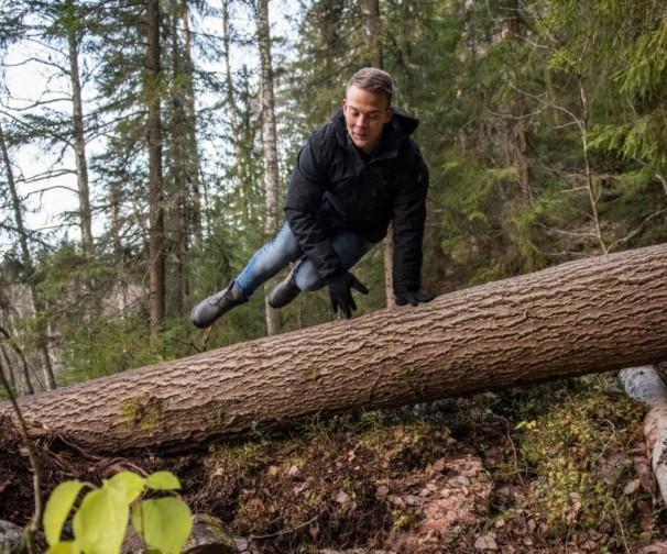 Mies hyppää kaatuneen puunrungon yli